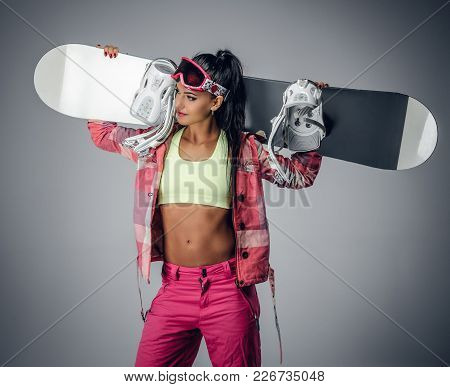 Positive Brunette Female Holding A Snowboard On Her Shoulder In A Studio On Grey Background