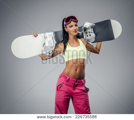 Sexy Female In Ski Costume Posing With Snowboard In A Studio On Grey Background.