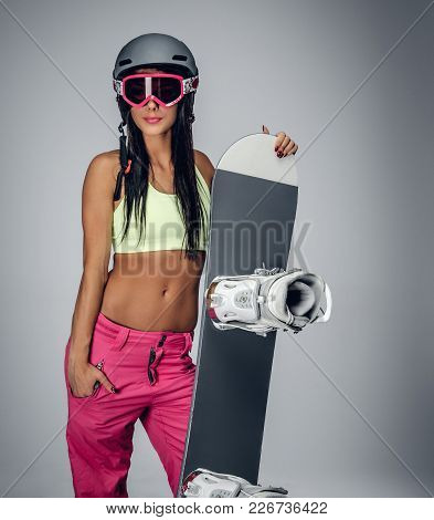 Smiling Brunette Female In A Pink Snowing Pants And Green T Shirt Holding Snowboard Isolated On Grey
