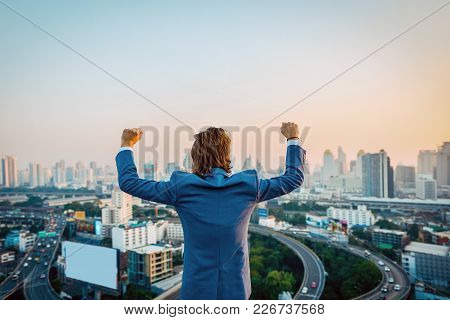 Successful Western Businessman With Hands Up Looking At The City At Sunset