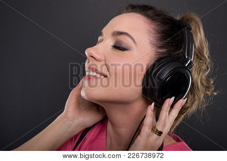 Close-up Of Beautiful Young Doctor Listening To Headphones