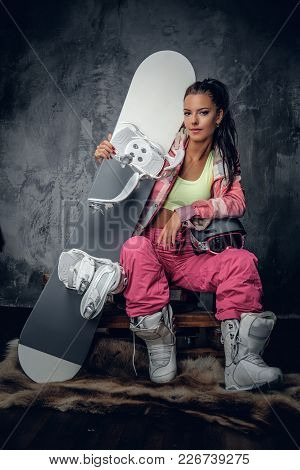 Attractive Young Female In A Pink Snowboarder Costume Holding Snowboard And Safety Helmet.