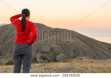The Girl Looks Into The Distance At The Mountains In The Red Fleece Jacket And Hiking Pants With His