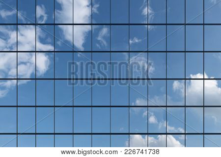 Wall Of Modern Business Skyscraper With Blue Windows In Day Sunlight Under Blue Sky With Clouds Rais