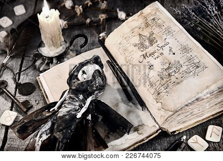 Old Book With Evil Spells, Scary Doll, Rune And Burning Candle On Planks. Halloween, Occult, Esoteri