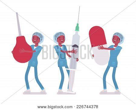 Male Nurse And Big Tools. Young Man In Hospital Uniform Holding Giant Enema, Syringe, Pill. Medicine