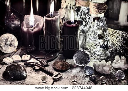Black Candles, Crystals And Stones, Ancient Runes, Key And Ritual Bottles On Witch Table. Halloween,