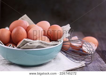 Brown Farm Fresh Chicken Eggs From Free Range Chickens With Whisk Over A Rustic Wooden Background.