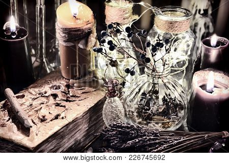 Evil Book With Black Candles, Glass Bottles, Poison Berries And Herbs On Witch Table. Halloween, Occ