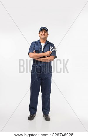 Indian Happy Auto Mechanic In Blue Suit And Cap Holding Spanner Tool In Action, Isolated Over White