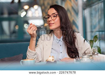 Sweet Life. Appealing Pensive Wistful Woman Eating Desert While Holding Fork And Enjoying Lunch