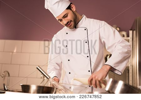Portrait Of Confectioner In Chef Hat Pouring Milk Into Bowl While Making Dough In Restaurant Kitchen