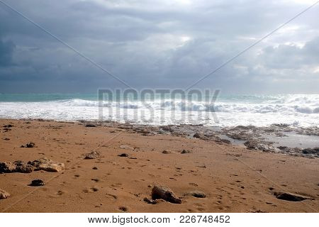 Landscape With Stormy Sea Waves Break About The Empty Wild Beach Against The Cloudy Sky On Overcast