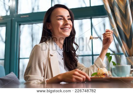 My Weakness. Elegant Dreamful Satisfied Woman Tasting Meal While Sitting Near Window And Grinning