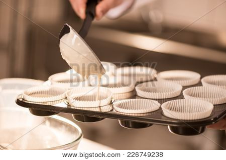 Partial View Of Confectioner Pouring Dough Into Baking Forms