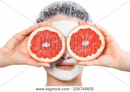 Girl With Fruit Mask On Face Holds Red Grapefruits At Eyes Level Isolated On White Background