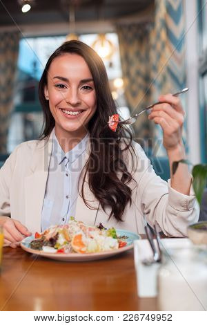 Delicious Salad. Irresistible Jolly Happy Woman Elevating Fork While Staring At The Camera And Sitti