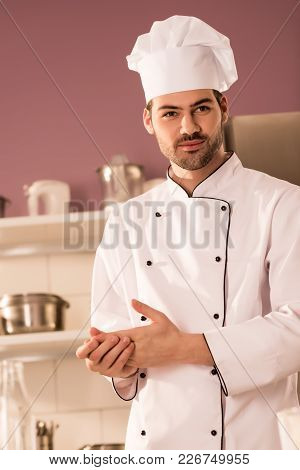 Portrait Of Handsome Confectioner In Chef Hat In Restaurant Kitchen