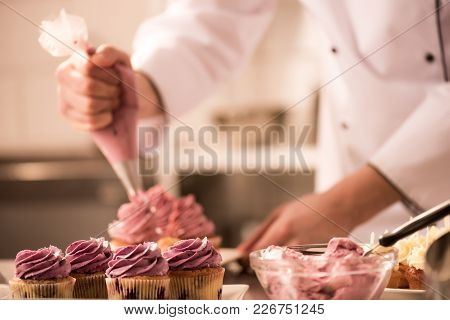 Cropped Shot Of Confectioner Putting Cream On Cupcakes