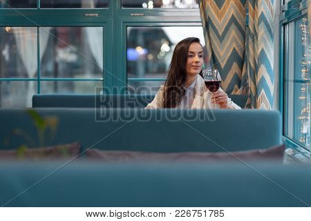 Sophisticated Taste. Thoughtful Pretty Wistful Woman Sitting At Cafe While Rising Glass Of Wine And