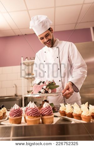 Smiling Confectioner Standing At Counter With Cake And Cupcakes In Restaurant Kitchen