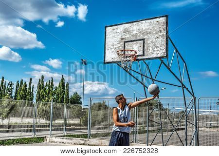 Player Shooting A Basketball In A Playground