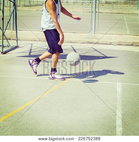 Basketball Player Dribbling In A Playground. Vintage Tone Effect