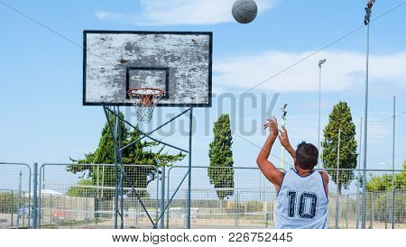 A Basketball Player Shooting In A Playground