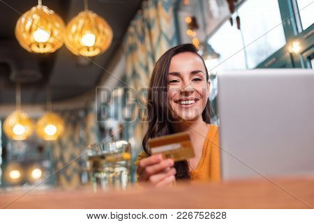 Payment Opportunities. Low Angle Of Positive Young Brunette Woman Carrying Credit Card While Smiling