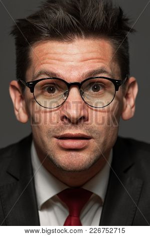 Close-up Portrait Of Curious Businessman In Formal Costume And Wearing Glasses On Gray Background