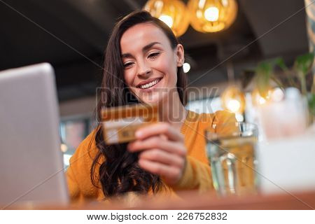 Payment Everywhere. Low Angle Of Sincere Pleasant Satisfied Woman Looking At Credit Card While Smili