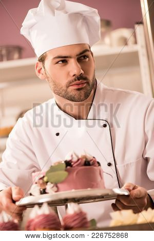 Portrait Of Confectioner With Cake In Hands Looking Away In Restaurant Kitchen
