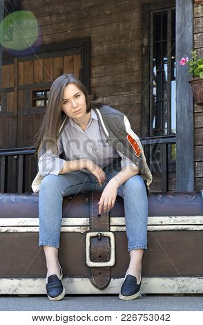 Girl Sitting On A Large Chest Against A Wooden Building, Girl In Jeans, Shirt And Sweatshirt, Portra