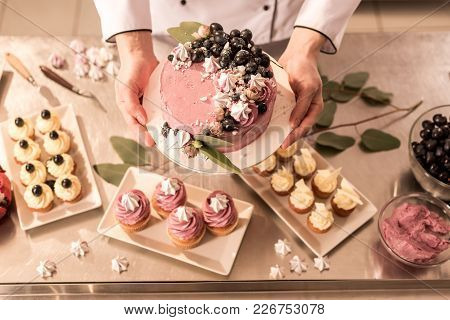 Partial View Of Confectioner Holding Cake In Hands In Restaurant Kitchen