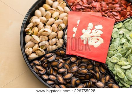 Traditional chinese snack tray for lunar new year, with red packet word meaning luck