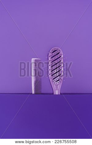 Close Up View Of Purple Hairbrush And Comb Isolated On Purple