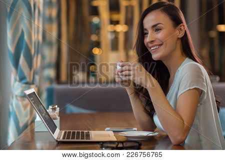 Big Opportunity. Satisfied Ambitious Female Freelancer Holding Cup While Sitting At Table And Using