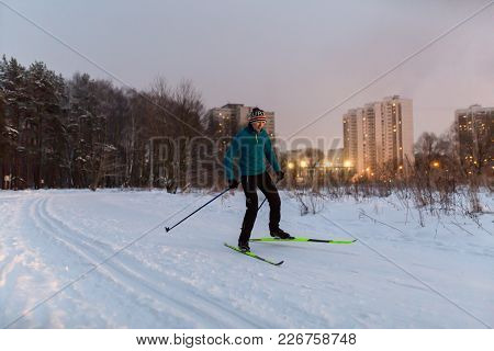 Picture Of Male Skier In Blue Jacket In Winter Park On Background Of Houses