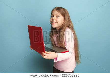 The Love Of The Computer. Teen Happy Girl With Notebook, Delight. The Smiling Teen Girl On A Blue St