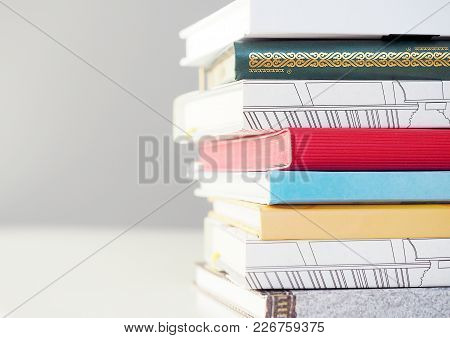 Pile Of Multi-color Books On White Table Close Up View