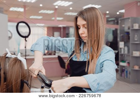 Close-up of master hairstylist ironing for straightening hair restores keratin and straightens hair. poster
