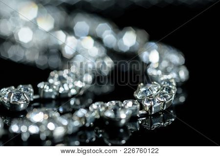 Silver Necklace With Diamonds Close-up In Defocus On A Black Background