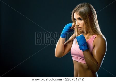 Fitness Woman With The Blue Boxing Bandages, Studio Shot On Dark Background. Space For Text. Athlete
