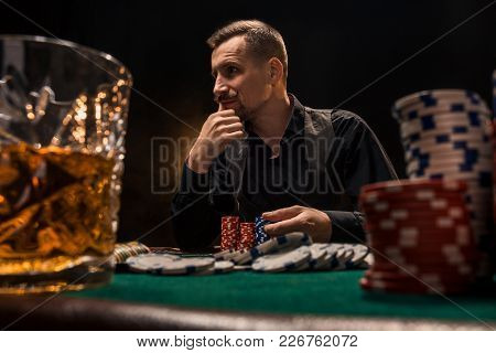 Young Handsome Man Sitting Behind Poker Table With Cards And Chips. On A Dark Background. In The For