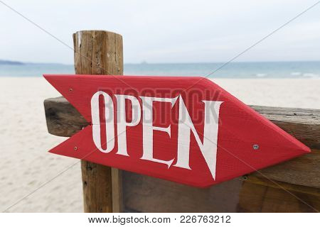 Sign Open On The Beach . Red Arrow