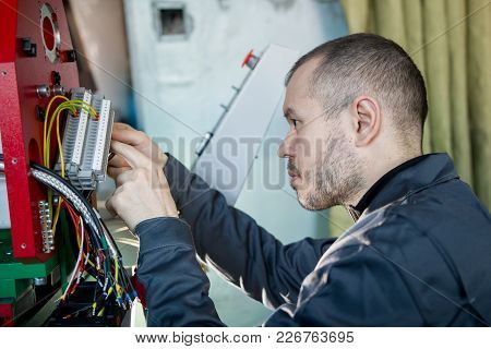 Electrician On Overalls Is Working With Energy Panel And Machinery Equipment On Plant, Close Up