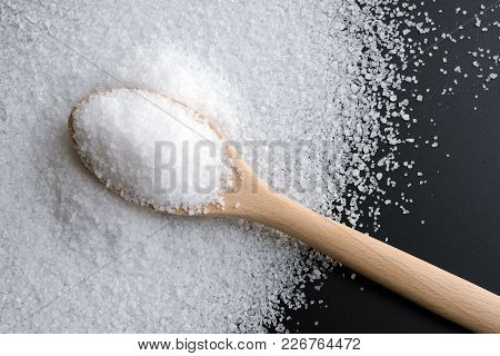 Sea Salt In A Large Wooden Spoon, Scattered On A Black Board
