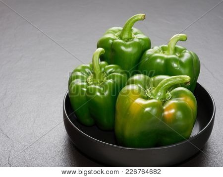 Green Bell Pepper Or Capsicum In Shallow Black Bowl Over Dark Background Show Concept Of Healthy Liv