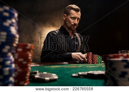 Young Handsome Man Sitting Behind Poker Table With Cards And Chips. In The Foreground Stacks Of Chip