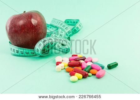 Dieting Concept With Natural Apple, Measuring Tape And Pills